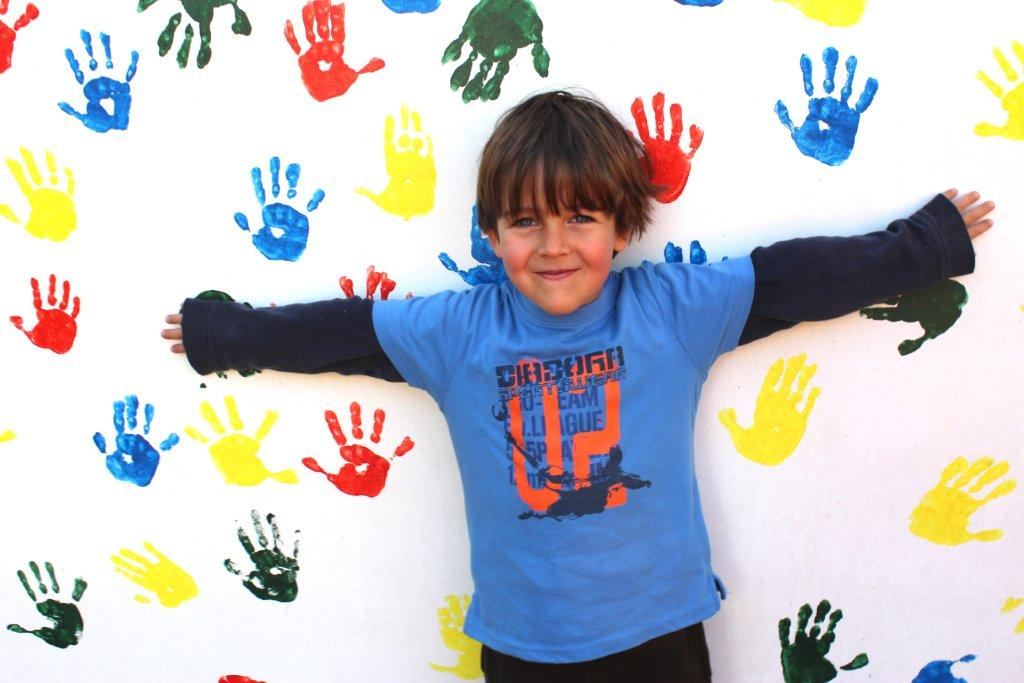 ילד מחייך ונשען עם הגב על קיר עם טביעות של כפות ידיים בצבעים
