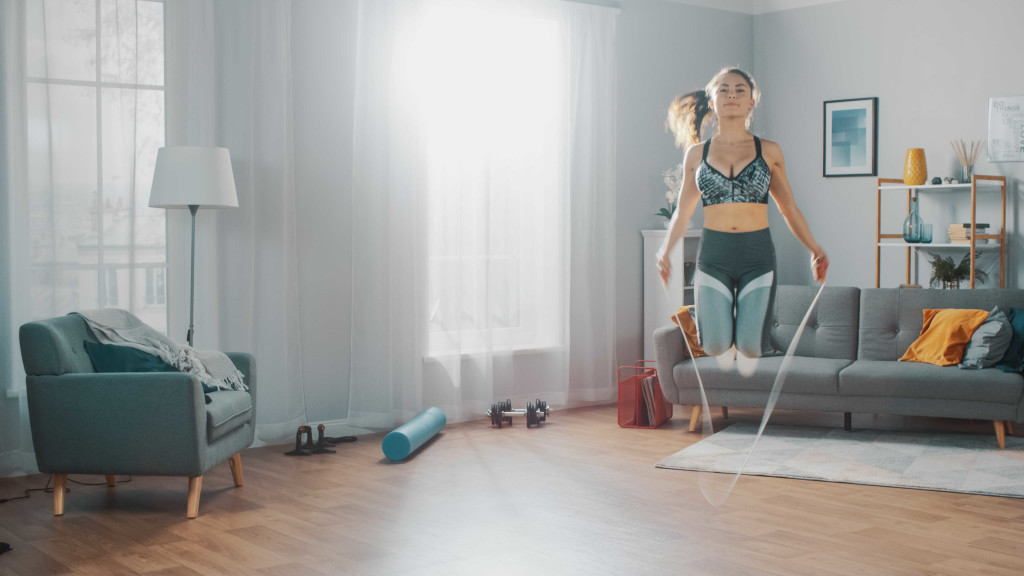 בחורה מבצעת אימון קפיצה בחבל בבית